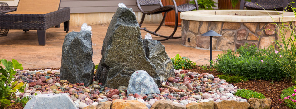 A bubbling rock water feature installed next to a new paver patio and fire pit at a home in Fort Collins.