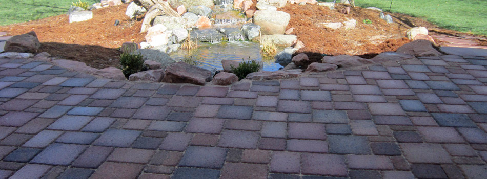New concrete paver patio installed next to a new water feature on a property in Windsor,CO.