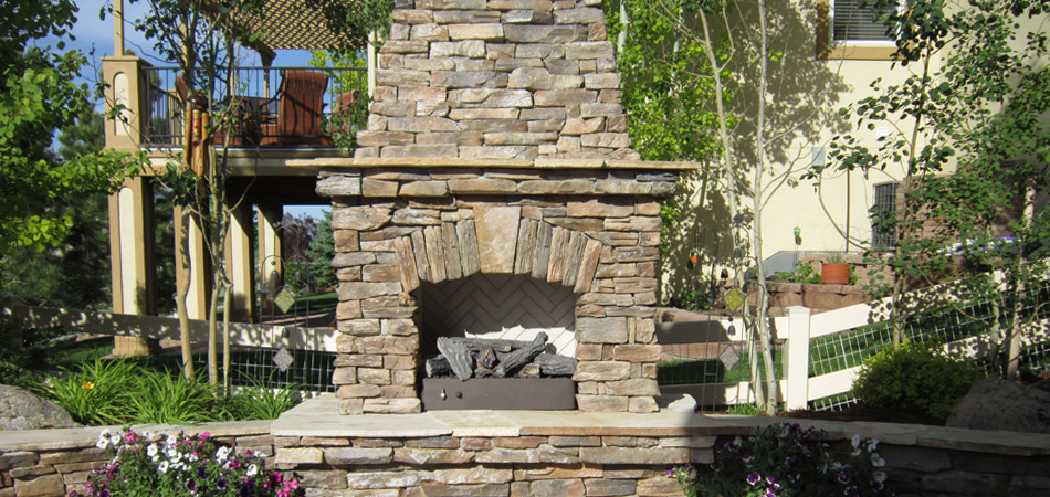 Outdoor fireplace built in Loveland that features natural stone.