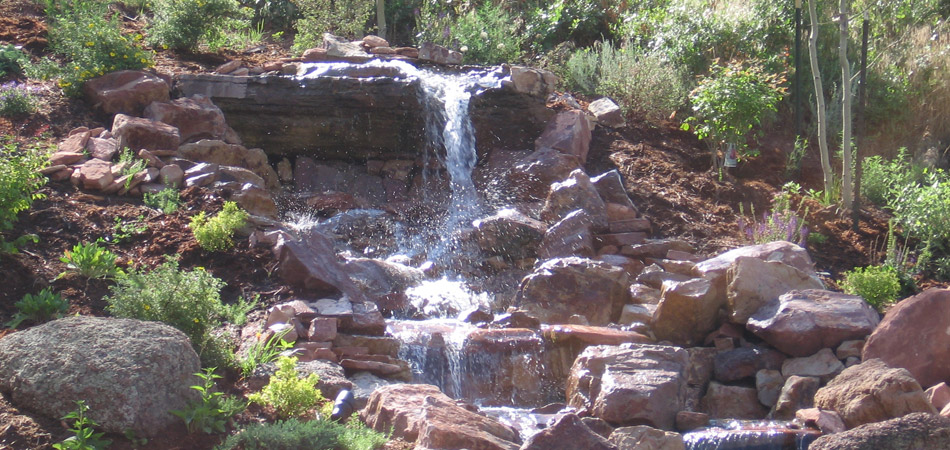 Stacked stone waterfall in Fort Collins that was designed and built by Alive Outside Landscaping.