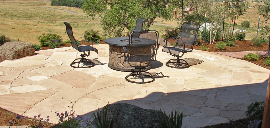 Outdoor fire pit with seating on a custom stone patio in Fort Collins, CO.