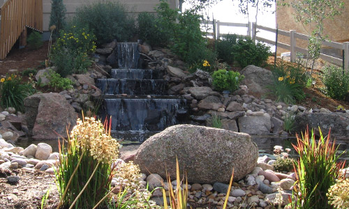 Water fall and boulder landscape in the backyard of a home in Windsor, CO.