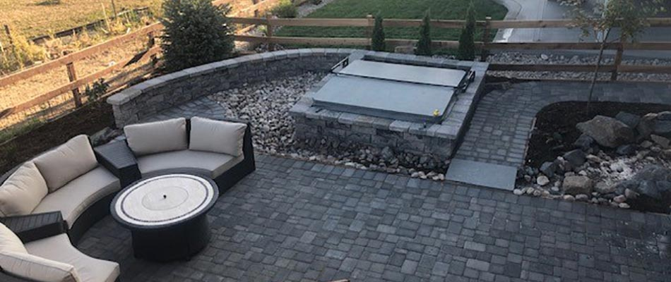 Custom outdoor paver patio with seating wall and gas fire pit in Fort Collins, CO.