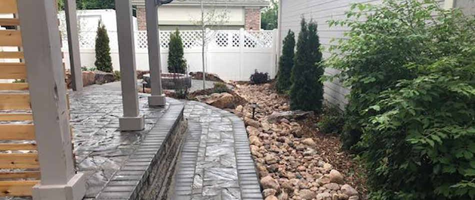 This custom landscaping and dry creek bed accentuates the hardscaping at this project in Denver, CO.